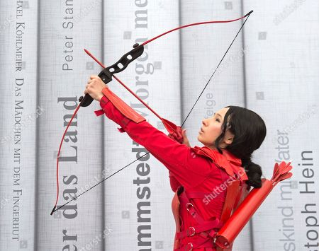 A cosplayer dressed in a fantasy costume performs the Katniss Everdeen figure, a fictional character and the protagonist of The Hunger Games trilogy by Suzanne Collins, during the Manga-Comic-Convention at the Leipzig International Book Fair in Leipzig, central Germany, . The fair is a meeting place for all comic book, manga, cosplay, Japan and gaming aficionados from around the world