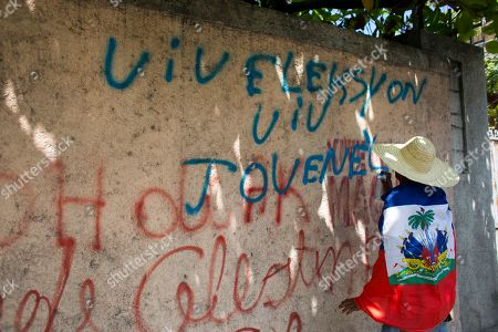 """A supporter of presidential candidate Jovenel Moise, from the PHTK political party, writes a message in Creole : """"Long live elections, long live Jovenel"""" during a protest demanding interim President Jocelerme Privert respect the upcoming election date in Port-au-Prince, Haiti, . The next election is scheduled for April 24. Haiti had been scheduled to hold a presidential and legislative second runoff on Jan. 24 but the now-splintered provisional electoral council canceled it for a second time amid protests and suspicion that the first round was marred by widespread fraud favoring Moise, the chosen candidate of former President Michel Martelly"""
