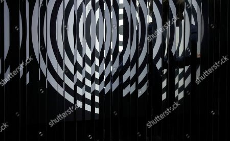 """A woman walks behind the artwork """"Cloison a lames reflechissantes"""" created by Argentina artist Julio Le Parc at Art Basel in Hong Kong. Asia's biggest exhibition of modern and contemporary art brought together 239 galleries from 35 countries and territories in Hong Kong, which has emerged as the region's top art trading hub"""