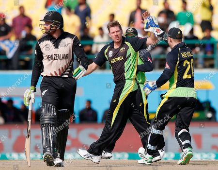 Australia's James Faulkner celebrates with teammate Peter Neville, right, after dismissing New Zealand's Martin Guptill, left, during their ICC World Twenty20 2016 cricket match at the Himachal Pradesh Cricket Association (HPCA) stadium in Dharamsala, India