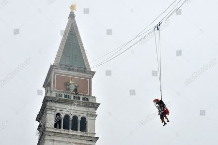 """Italian musician Saturnino Celani, wearing a Carnival costume, descends from the bell tower in St. Mark's Square for the traditional Flight of the Eagle (Volo dell'Aquila), on the last Sunday of the Venice Carnival, in Venice's St. Mark's Square, . The musician is attached by wires, """"flies"""" over the crowd, starting from St. Mark's bell tower and gradually descends to the square in one of the carnival's main crowd-pleaser events"""