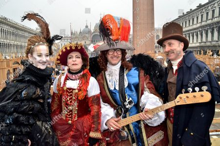"""Italian musician Saturnino Celani, second from right, holds his bass after and poses for photographers with other carnival participants after he descended from the bell tower in St. Mark's Square during the traditional Flight of the Eagle (Volo dell'Aquila), on the last Sunday of the Venice Carnival, in Venice, . The musician, attached by wires, """"flies"""" over the crowd, starting from St. Mark's bell tower and gradually descends to the square in one of the carnival's main crowd-pleaser events"""