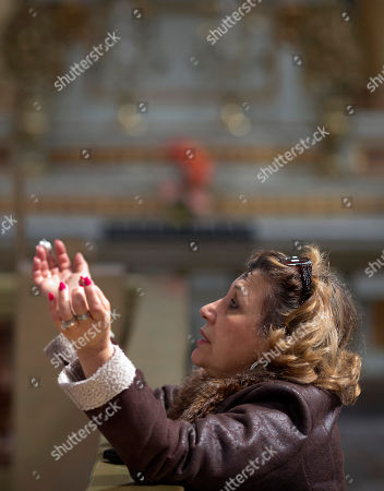 A Catholic woman with her forehead marked with an ashen cross prays during an Ash Wednesday Mass at the Metropolitan Cathedral in Mexico City, . Pope Francis will arrive to Mexico on Friday, Feb. 12 for a week-long visit
