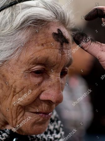 A Catholic woman has her head marked with an ashen cross during an Ash Wednesday Mass at the Metropolitan Cathedral in Mexico City, . Pope Francis will arrive in Mexico on Friday, Feb. 12 for a week-long visit