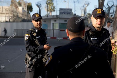 Israeli police officers stand at the entrance of the prison where Former Israeli Prime Minister Ehud Olmert will arrive to begin his sentence, in the central Israeli town of Ramle, Israel, . Olmert made a last-minute plea to salvage his legacy on Monday, appealing to Israelis to remember his peace-making attempts as leader and denying any wrongdoing in the bribery charges against him just hours before he headed to prison