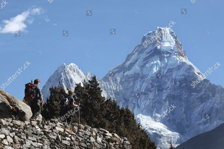 Trekkers make their way to Dingboche, a popular Mount Everest base camp, in Pangboche, Nepal. Officials say three foreign climbers; two British Kenton Cool, Robert Richard Lucas, and Mexican David Liano Gonzalez along with three Nepalese guides have scaled Mount Everest, the first foreigners to reach the summit in two years
