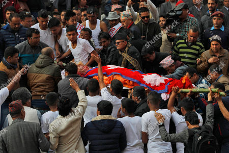 Supporters carry the body of former Nepalese prime minister Sushil Koirala, for cremation on the banks of the Bagmati River in Kathmandu, Nepal, . Koirala, who was a key figure in the drafting and adoption of the country's new constitution in 2015, died Tuesday at the age of 78