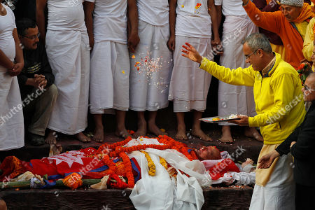 A Hindu priest performs rituals during the cremation of Nepalese prime minister Sushil Koirala, on the banks of the Bagmati River in Kathmandu, Nepal, . Koirala, who was a key figure in the drafting and adoption of the country's new constitution in 2015, died Tuesday at the age of 78