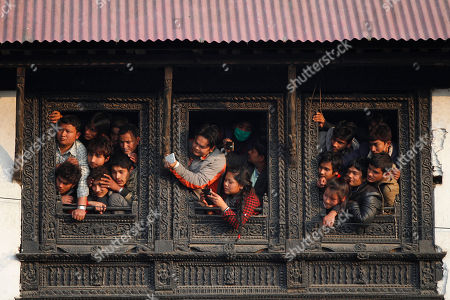Nepalese people watch from the window of a Hindu temple the cremation of Nepalese prime minister Sushil Koirala, on the banks of the Bagmati River in Kathmandu, Nepal, . Koirala, who was a key figure in the drafting and adoption of the country's new constitution in 2015, died Tuesday at the age of 78