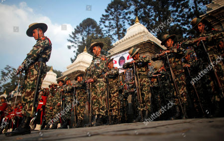 Nepalese army soldiers give a guard of honor during the cremation of Nepalese prime minister Sushil Koirala, on the banks of the Bagmati River in Kathmandu, Nepal, . Koirala, who was a key figure in the drafting and adoption of the country's new constitution in 2015, died Tuesday at the age of 78