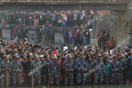 Nepalese policemen guard as people gather during the cremation of Nepalese prime minister Sushil Koirala, on the banks of the Bagmati River in Kathmandu, Nepal, . Koirala, who was a key figure in the drafting and adoption of the country's new constitution in 2015, died Tuesday at the age of 78