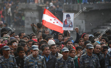 A supporter holds the Nepali congress Party flag during the cremation of Nepalese prime minister Sushil Koirala, photograph seen, on the banks of the Bagmati River in Kathmandu, Nepal, . Koirala, who was a key figure in the drafting and adoption of the country's new constitution in 2015, died Tuesday at the age of 78