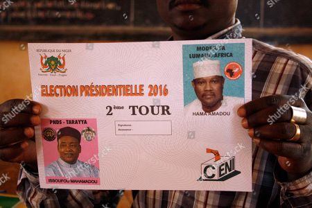 Stock Image of An election official displays a ballot paper with the image of Niger incumbent President Mahamadou Issoufou, left, and opposition leader Hama Amadou, right, at a polling station, during the election, in Niamey, Niger, . Niger's president is running for a second term against an opponent who had to campaign from behind bars before being flown last week to Paris for medical treatment. President Mahamadou Issoufou finished first in the first round of balloting last month but without the majority he needed to avoid a second round