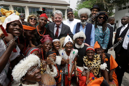 Germany President Joachim Gauck, center, and playwright and poet Wole Soyinka, of Nigeria, recipient of the 1986 Nobel Prize in Literature, center right, pose for the media with traditional dancers during a visit to Freedom Park in Lagos, Nigeria