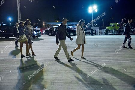 Stock Picture of Barack Obama, Michelle Obama, Malia Obama, Sasha Obama, Marian Robinson President Barack Obama followed by first lady Michelle Obama, daughters Malia and Sasha and first lady's mother Marian Robinson, walk across the tarmac before boarding Air Force One at Ezeiza Airport in Buenos Aires, Argentina, . Early today the first family visited Bariloche, a picturesque city in southern Argentina, before departing for a return flight to Washington