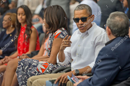Barack Obama, Raul Castro, Malia Obama, Sasha Obama, Michelle Obama, Marian Robinson President Barack Obama talks with Cuban President Raul Castro, right, as they attend an exhibition baseball game between the Tampa Bay Rays and the Cuban National team at the Estadio Latinoamericano, in Havana, Cuba. Also attending are members of the first family from l-r, first lady's mother Marian Robinson, Malia Obama, Sasha Obama and first lady Michelle Obama