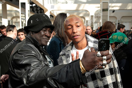 Pharell Williams poses for a selfie with a fashion guest after Chanel's Fall-Winter 2016-2017 ready to wear fashion collection presented in Paris