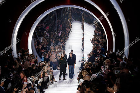 Swiss designers Serge Ruffieux, right, and Lucie Meier acknowledge applause at the end of Christian Dior's Fall-winter 2016-2017 ready to wear collection presented in Paris, France
