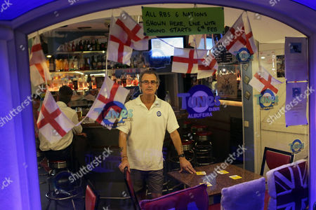 """In this picture taken, Michael Wood poses for a photo behind the window of his bar in Albufeira, in southern Portugal's Algarve region. Some of Wood's best business, he says, comes from Britons on what they call the """"cigarette run"""", a quick trip to Portugal on a low-cost flight to buy dozens of cartons of cigarettes, which are about 30 percent cheaper than in the U.K"""
