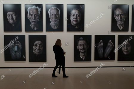 "A woman looks at the art piece pictures called ""Our House Is On Fire"" by Iranian born artist Shirin Neshat as a part of the Arab modern art exhibition ""Looking at the World Around You: Contemporary Works from Qatar Museums"", in Madrid"
