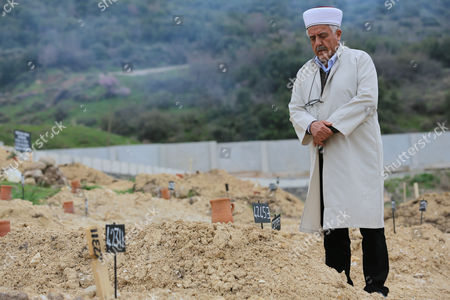 "Ahmet Altan prays at the graves marked with numbers of unidentified migrants drowned at Aegean Sea in Izmir, Turkey. The journey for thousands of migrants headed to Europe often begins at an innocuous park in the Aksaray neighborhood of Istanbul which is so central to the human trafficking business that would-be passengers and dealers refer to it simply as ""smugglers square."" Turkey has become the main departure point for refugees --- not only from Syria but also Iraq and Afghanistan -- who view Europe as their best shot at safety and a better life"