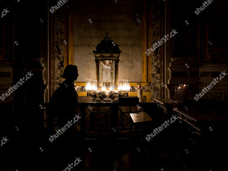 """A woman pauses in front of the statue of the """"Bambino di San Gaetano"""" (St. Gaetano Baby) in the Rome's St. Andrea della Valle Church, . The wooden statue of St. Gaetano Baby was venerated by the Romans since 1800"""