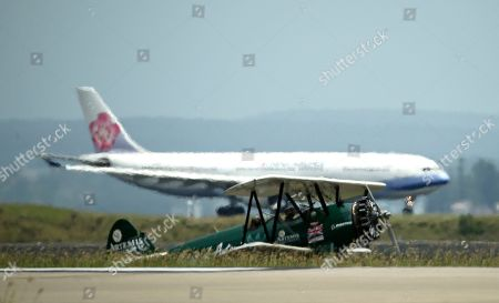 British aviator Tracey Curtis-Taylor taxies her 1942 Boeing Stearman Spirit of Artemis aircraft past a modern airliner after she arrived at Sydney Airport in Sydney, Australia, . The 53 year-old aviator set out from Britain in October 2015 to recreate Amy Johnson's 1930 flight from Britain to Australia, a 13,000-mile solo flight in a vintage open cockpit biplane fling across 23 countries