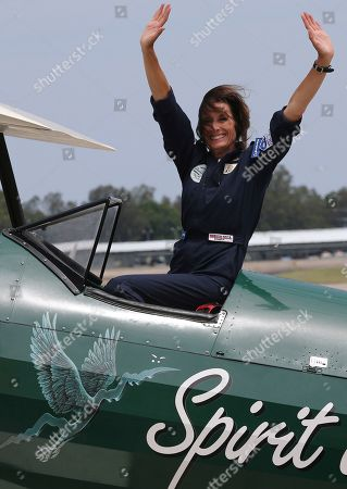 British aviator Tracey Curtis-Taylor waves her arms as she celebrates completing a 13,000 mile solo flight in her 1942 Boeing Stearman Spirit of Artemis aircraft at Sydney Airport in Sydney, Australia, . The 53 year-old aviator set out from Britain in October 2015 to recreate Amy Johnson's 1930 flight from Britain to Australia, a 13,000-mile solo flight in a vintage open cockpit biplane fling across 23 countries