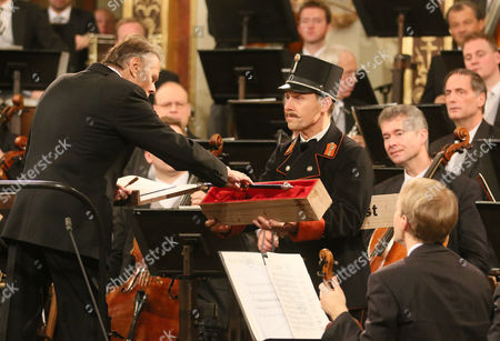 Latvian Maestro Mariss Jansons, left is presented a new conductor's buton during the traditional New Year's concert with the Vienna Philharmonic Orchestra at the golden hall of the Musikverein in Vienna, Austria