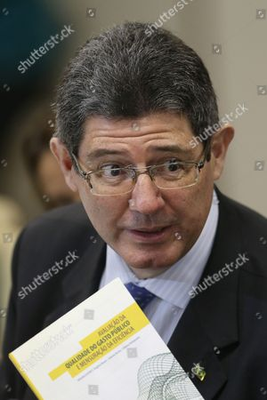 "Joaquim Levy Brazil's Economy Minister Joaquim Levy holds a booklet titled in Portuguese ""Evaluation of Public Spending Quality"" during a breakfast with journalists at the Economy Ministry in Brasilia, Brazil, . Fitch Ratings cut Brazil's credit to junk status Wednesday, the second of the big three agencies to rip away the nation's hard-won investment grade status and igniting fears that the recession enveloping Latin America's biggest economy will last longer than expected"