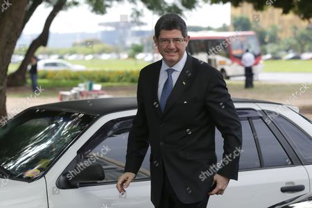 Joaquim Levy Brazil's Economy Minister Joaquim Levy arrives for a breakfast with journalists at the Economy Ministry in Brasilia, Brazil, . Fitch Ratings cut Brazil's credit to junk status Wednesday, the second of the big three agencies to rip away the nation's hard-won investment grade status and igniting fears that the recession enveloping Latin America's biggest economy will last longer than expected