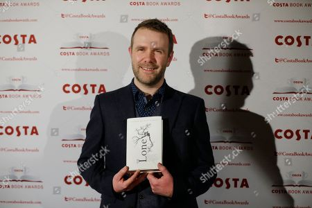 The winner of the first novel category Andrew Michael Hurley poses for photographs with his book 'The Loney' at the Costa Book Awards in London