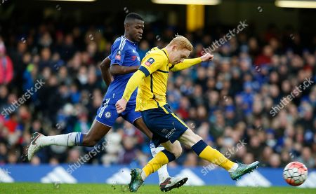 Scunthorpe United's Luke Williams, front, takes a shot on goal watched by Chelsea's Ramires during the English FA Cup third round soccer match between Chelsea and Scunthorpe United at Stamford Bridge stadium in London