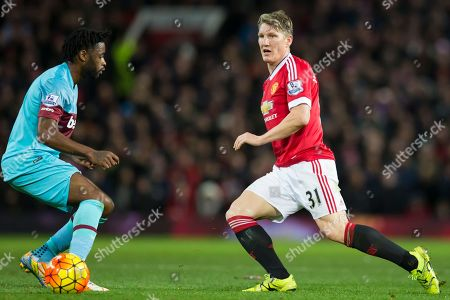 Manchester United's Bastian Schweinsteiger, right, fights for the ball against West Ham United's Alexandre Song during the English Premier League soccer match between Manchester United and West Ham United at Old Trafford Stadium, Manchester, England