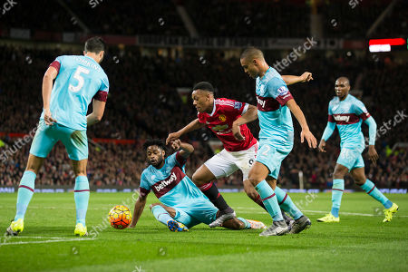 Manchester United's Anthony Martial, centre, fights for the ball against West Ham United's Alexandre Song, centre left, and Winston Reid, centre right, during the English Premier League soccer match between Manchester United and West Ham United at Old Trafford Stadium, Manchester, England