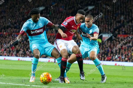 Manchester United's Anthony Martial, centre, fights for the ball against West Ham United's Alexandre Song, left, and Winston Reid during the English Premier League soccer match between Manchester United and West Ham United at Old Trafford Stadium, Manchester, England