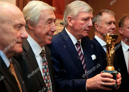 Four members of the England 1966 World Cup winning side from left, George Cohen, Gordon Banks, Martin Peters and Geoff Hurst pose for the media with the official English Football Association replica of the Jules Rimet trophy, at the Royal Garden Hotel in London . The FA will hold an exhibition in London and Manchester showing memorabilia from England's only World Cup win in 1966 during the 50th anniversary of the event in 2016