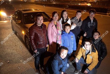 Real estate agent Chen Xiao, top center in white, poses with passengers from left top, He Shaolei, Han Ajuan, Han's son Miao Ruijing, Zhang Tao and Li Jin before they start their journey back to their hometown for the upcoming Chinese Lunar New Year, in Shanghai, China. They met on the ride-share app of Didi Chuxing, an Uber-like mobile car-hailing service. Carpooling is still unusual in China, but government officials welcome the idea as a way to alleviate the enormous burden placed on the public transportation system during the Lunar New Year holidays, China's most important vacation period when hundreds of millions travel to their hometowns. Three others in bottom are another group, from left, Zhang Xiaohui, Yang Chuang and Xu Peng