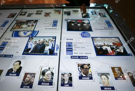 A visitor, top, looks at an electronic screen displaying images and convicted corruption charges of China's fallen politicians, Bo Xilai, bottom second right, Zhou Yongkang, bottom left, and other senior officials, at the China Court Museum in Beijing, . A court in northern China sentenced a former vice minister of public security to 15 years in jail on Tuesday for accepting bribes, state media reported. Li Dongsheng is the latest senior figure to fall in President Xi Jinping's anti-corruption crackdown that has targeted scores of high-level officials, including figures linked to China's former state security chief, Zhou. Zhou, the biggest tiger to fall, was once seen as a potent rival of Xi and was at the center of a vast patronage system from his various positions of power