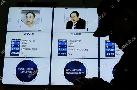 A visitor walks past an electronic screen displaying images of China's fallen politicians, Bo Xilai, left, and Zhou Yongkang, and their convicted corruption charges, at the China Court Museum in Beijing, . A court in northern China sentenced a former vice minister of public security to 15 years in jail on Tuesday for accepting bribes, state media reported. Li Dongsheng is the latest senior figure to fall in President Xi Jinping's anti-corruption crackdown that has targeted scores of high-level officials, including figures linked to China's former state security chief, Zhou. Zhou, the biggest tiger to fall, was once seen as a potent rival of Xi and was at the center of a vast patronage system from his various positions of power