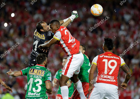 Marcos Díaz, Daniel Angulo Marcos Diaz goalkeeper of Argentina's Huracan, top left, jumps for the ball with Daniel Angulo of Colombia's Independiente Santa Fe during a Copa Sudamericana final soccer match in Bogota, Colombia