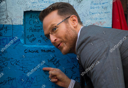 """Josh Lawson House of Lies"""" actor Josh Lawson points to his name scrawled on a wall outside the Bodeguita Del Medio bar during filming, in Havana, Cuba. There are so few international-quality hotel rooms that Cuba-based producers regularly cancel shoots due to lack of beds for cast and crew. """"House of Lies"""" stars good-naturedly described missing sheets and paper-thin pillows at the hotel where they stayed"""