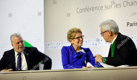 Quebec Premier Philippe Couillard, left, Ontario Premier Kathleen Wynne, center, and Manitoba Premier Greg Selinger attend a signing ceremony at the COP21, the United Nations Climate Change Conference in Le Bourget, north of Paris. The Paris conference is the 21st time world governments are meeting to seek a joint solution to climate change. The talks are focused on reducing emissions of carbon dioxide and other greenhouse gases, primarily by shifting from oil, coal and gas to cleaner sources of energy