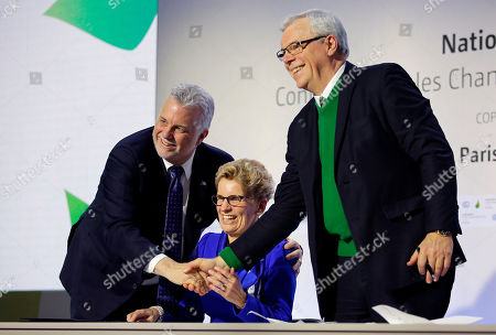 Quebec Premier Philippe Couillard, left, Ontario Premier Kathleen Wynne, center, and Manitoba Premier Greg Selinger shake hands during a signing ceremony at the COP21, the United Nations Climate Change Conference in Le Bourget, north of Paris. The Paris conference is the 21st time world governments are meeting to seek a joint solution to climate change. The talks are focused on reducing emissions of carbon dioxide and other greenhouse gases, primarily by shifting from oil, coal and gas to cleaner sources of energy
