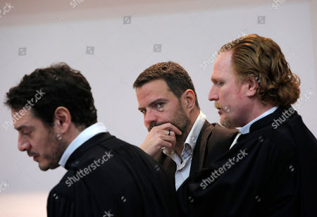 Jerome Kerviel, center, his lawyers David Koubbi, left, and Benoît Pruvost wait inside the Versailles appeal court, outside Paris, . Jerome Kerviel, convicted of the trading fraud that nearly brought down the French bank Societe Generale, is back in court to fight the 4.9 billion euros ($5.34 billion) in damages he had been ordered to pay for his ex-employer's losses