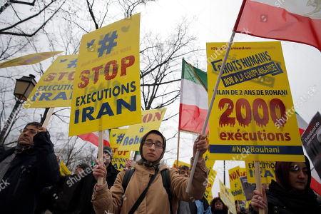 """Supporters of Maryam Rajavi, President of the National Council of Resistance of Iran, demonstrate against Iranian President Hassan Rouhani's visit in Paris, . Rouhani says his first visit to Europe since the nuclear accord was signed has proven that there are """"great possibilities"""" for economic, academic, scientific and cultural cooperation and that """"today we are in a win-win situation"""" after years of mutual losses due to sanctions. Banner on the right reads """" Human rights. No complaisance. 2000 executions after 2 years with Rohani"""