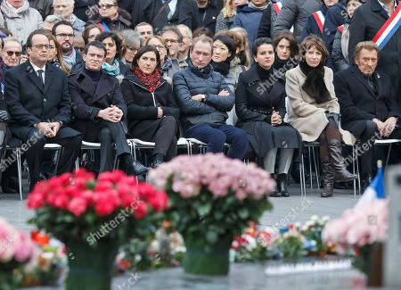 From left, France's President Francois Hollande, French Prime Minister Manuel Valls, an unidentified woman, former mayor of Paris Bertrand Delanoe, French Education Minister Najat Vallaud-Belkacem, French Social Affairs and Health Minister Marisol Touraine and French rocker star Johnny Hallyday attend a ceremony to honour the victims of the Islamic extremist attacks at Place de la Republique in Paris, . French President Francois Hollande and other dignitaries are holding a special ceremony to honor all those killed in Islamic extremist attacks around Paris in 2015, a year when the European way of life was targeted time and again with deadly consequences