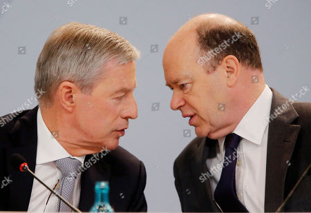 Co-CEOs of Deutsche Bank John Cryan, right, and Juergen Fitschen talk to each other during the annual press conference in Frankfurt, Germany