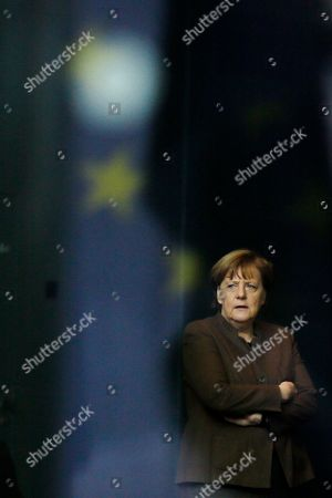 Through a window with a reflection of the European flag, German Chancellor Angela Merkel waits for the arrival of the Prime Minister of Slovenia Miroslav Cerar for a meeting at the chancellery in Berlin, Germany