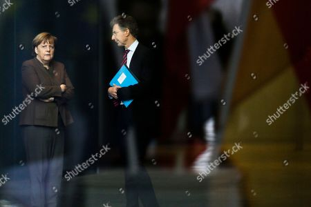 Through a window with reflections, German Chancellor Angela Merkel, left, talks to foreign policy advisor Christoph Heusgen between meetings with Jean-Claude Juncker, President of the European Commission and Miroslav Cerar, Prime Minister of Slovenia, at the chancellery in Berlin, Germany